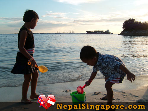 Kids enjoying playing in sand in Sentosa Island